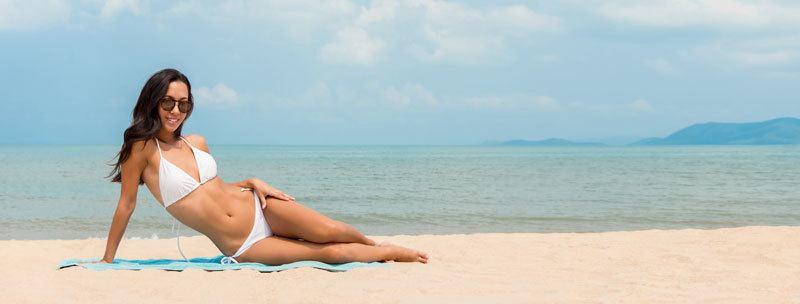 mladá žena na pláži opaľovacie krémy